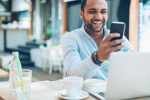 Man smiling at his phone showing that he is happy with the Microsoft Licensing Optimization he received